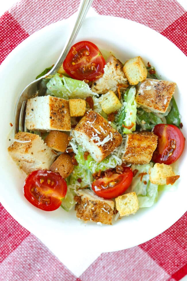 Close-up top view of Caesar chicken salad in a bowl.