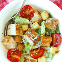 """Close-up of chicken salad in bowl. Text overlay """"The Best Easy Homemade Caesar Salad Dressing"""" and """"thatspicychick.com""""."""