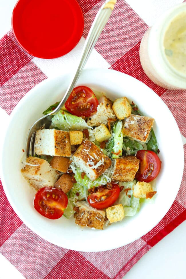 Bowl with chicken Caesar salad on a checkered red and white napkin. Dressing in jar behind.