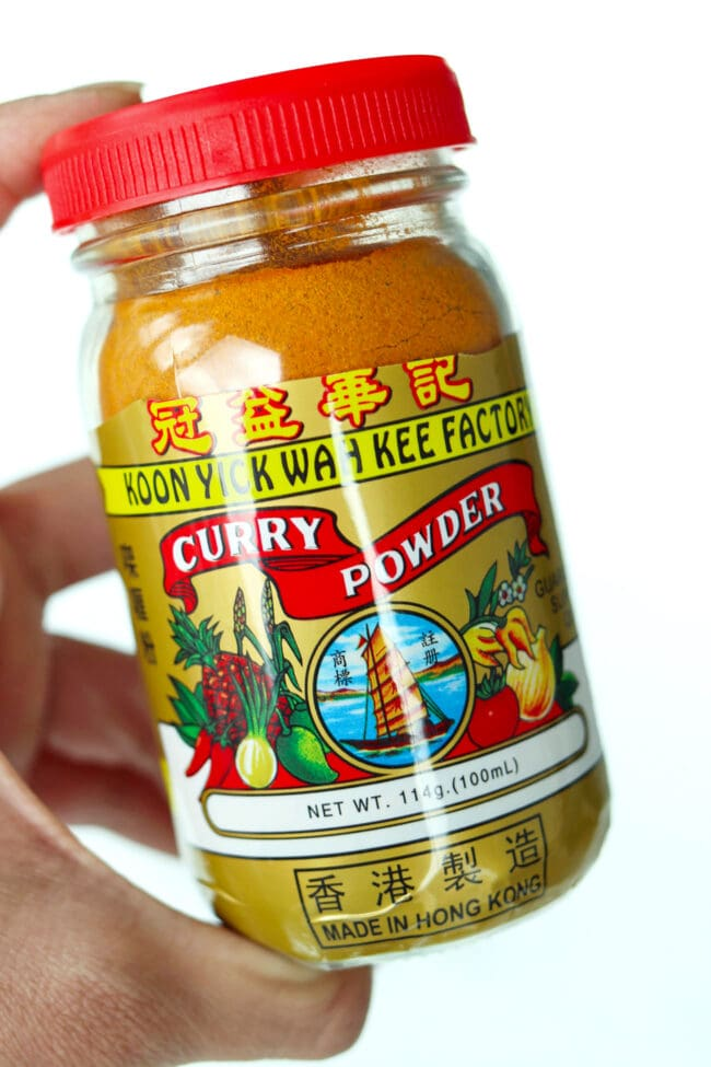 Hand holding up a curry powder bottle.