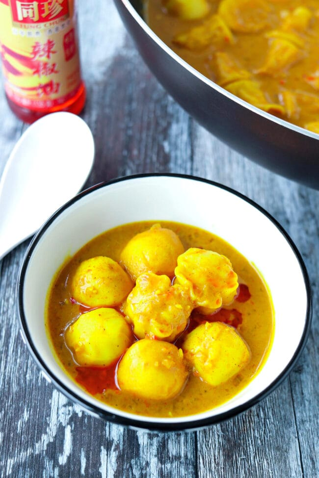 Front view of bowl with curry fish balls and shu mai with chili oil drizzle.