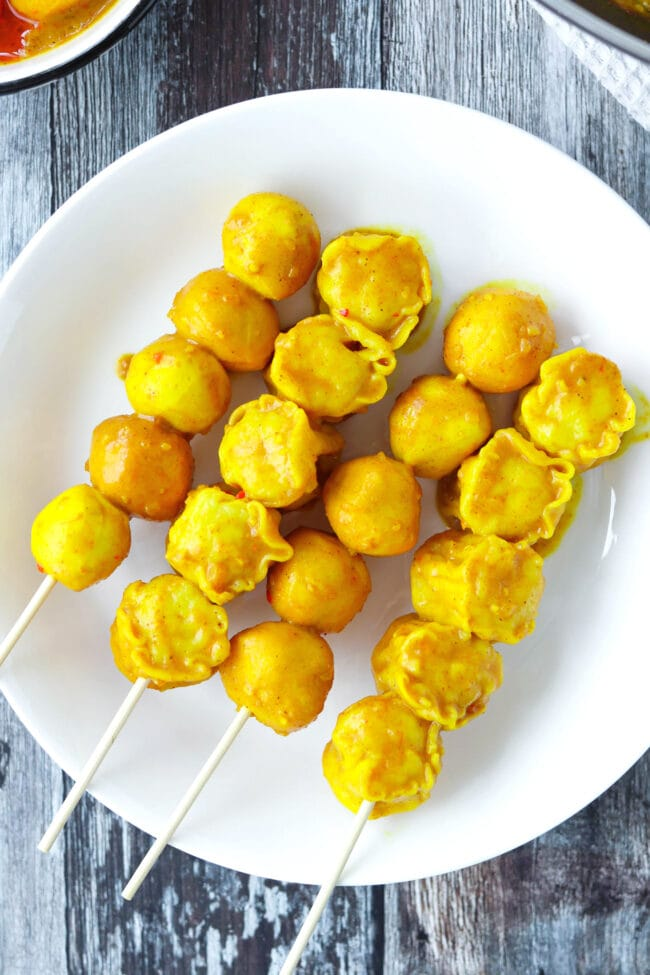 Top view of fish balls and shu mai skewers on a plate.