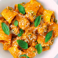 Close-up top view of plate with Spicy Pumpkin Vodka Pasta garnished with grated cheese and basil.