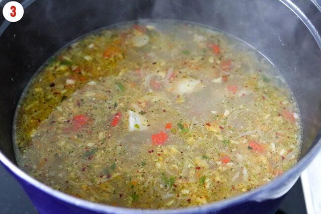 Seasoned pork rib soup in Dutch oven on stovetop.