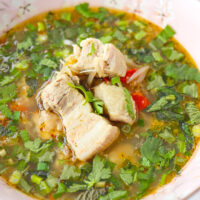 """Close-up front view of soup in a bowl. Text overlay """"Thai Spicy Pork Rib Soup"""", """"With Tender & Juicy Spare Ribs!"""", and """"thatspicychick.com""""."""