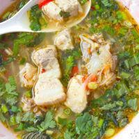 """Close-up of pork rib soup in a bowl with a spoon. Text overlay """"Thai Spicy Pork Rib Soup"""", """"With Tender & Juicy Spare Ribs!"""", and """"thatspicychick.com""""."""
