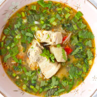 """Close-up top view of pork soup in a bowl. Text overlay """"Thai Spicy Pork Rib Soup"""", """"Delicious Hot & Sour Broth"""", and """"thatspicychick.com""""."""